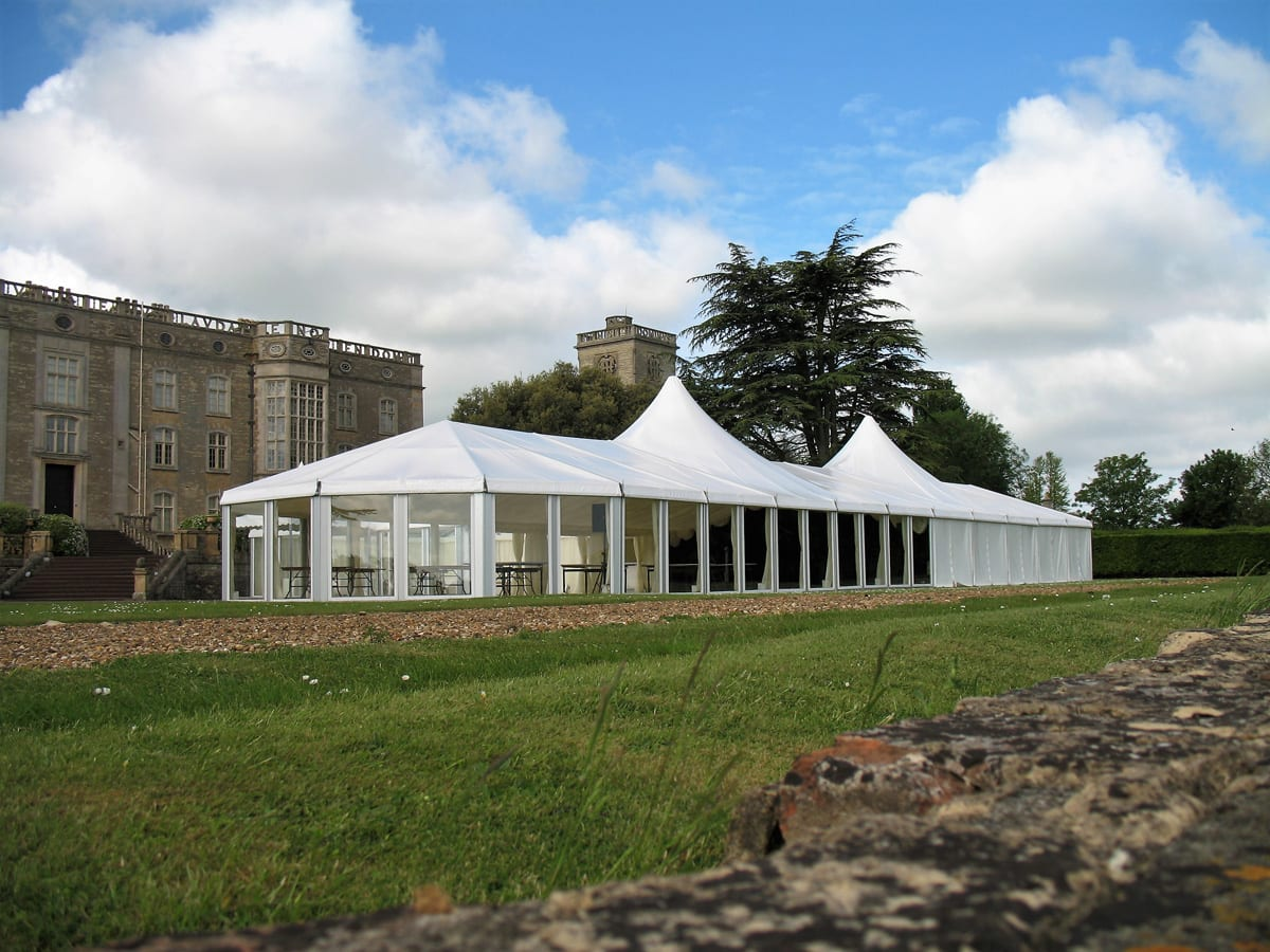 A HÖCKER P Series high peak roof heavy duty party tnt being used for a function next to a castle