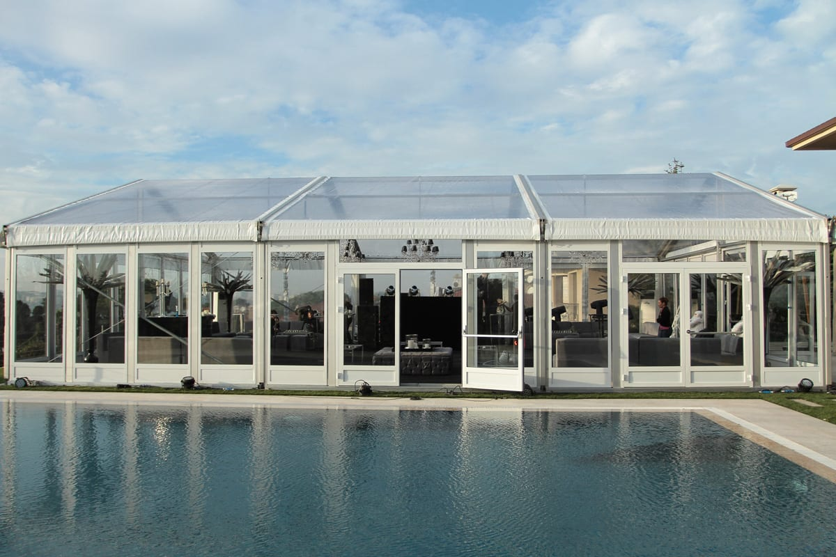 A HTS tentiQ GZ premium large party tent used as a lounge area next to a swimming pool