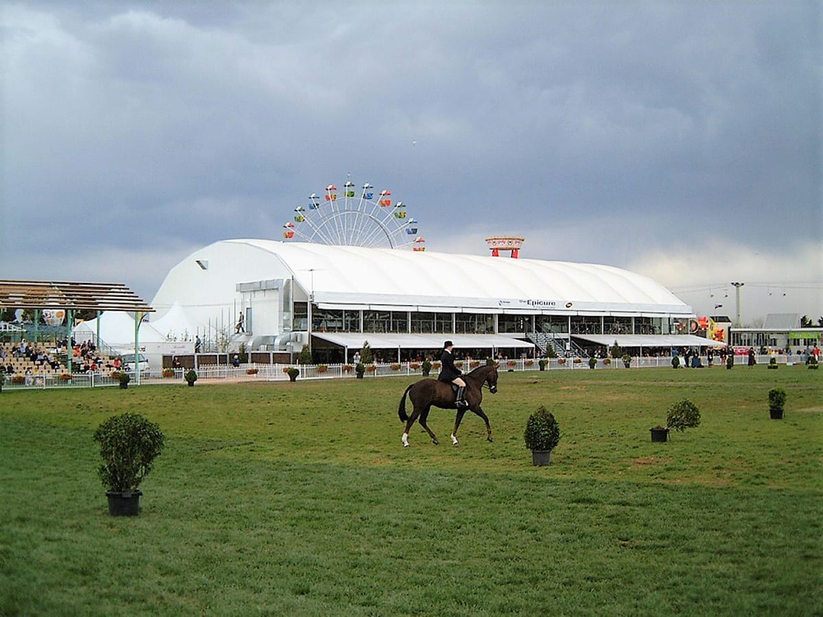 A multi-level curved roof structure with a balcony for spectator viewing at an equestrian event