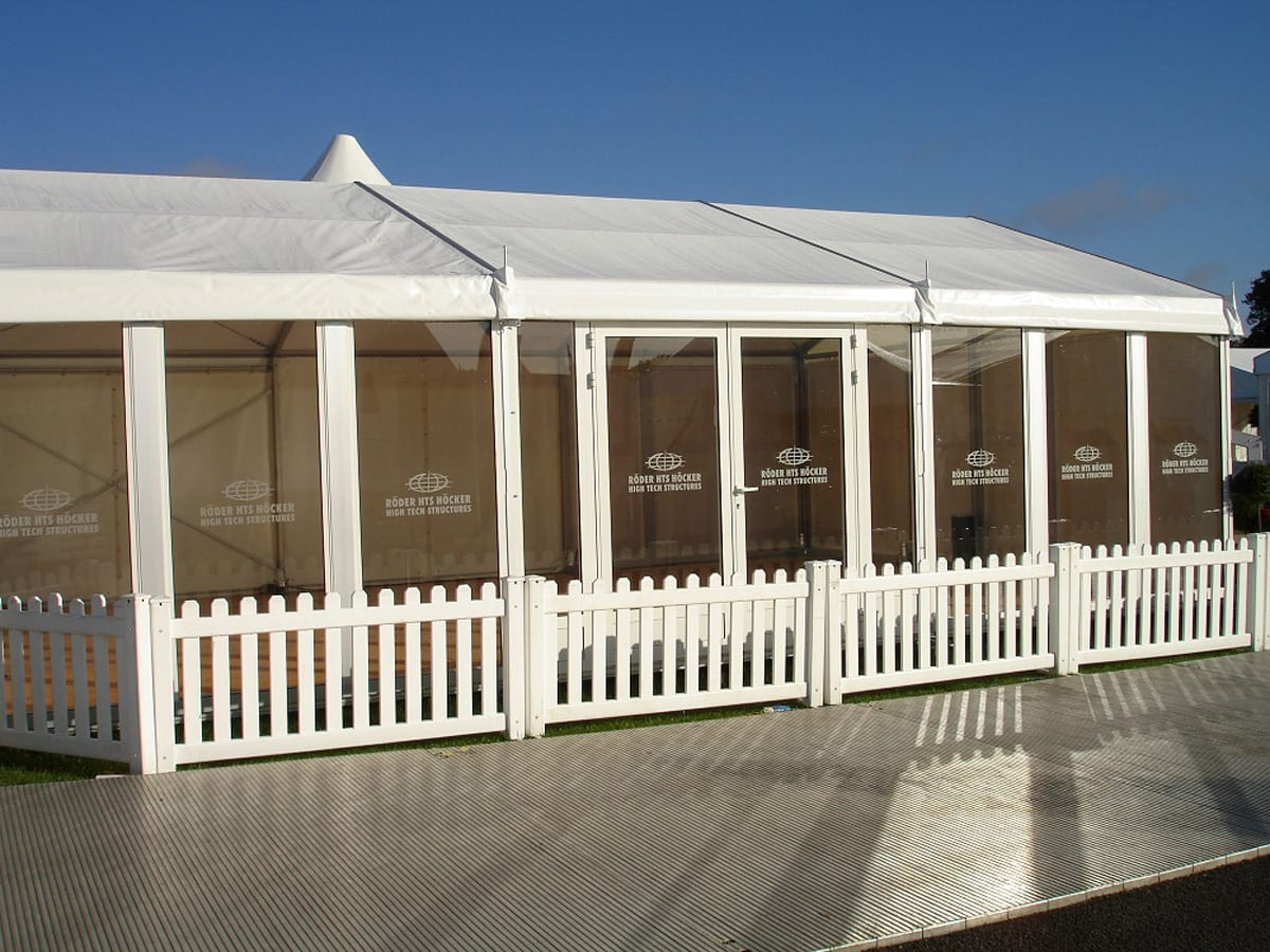 A RÖDER HTS (PZ) A-frame small party tent with surrounding fence at a trade show