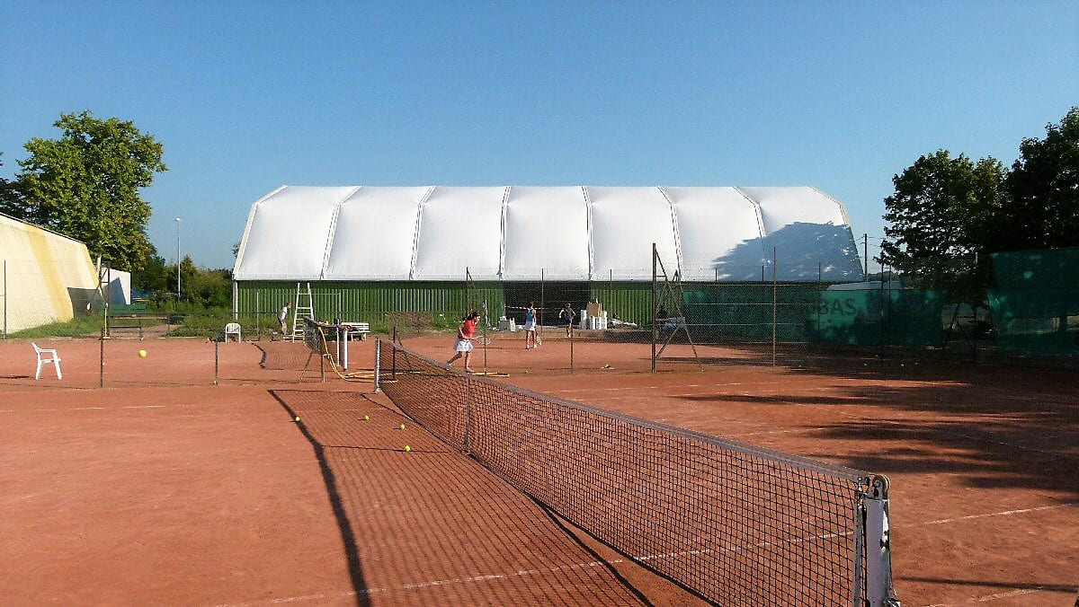 A Sports structure canopy with corrugated steel sheet walls next to a tennis courts