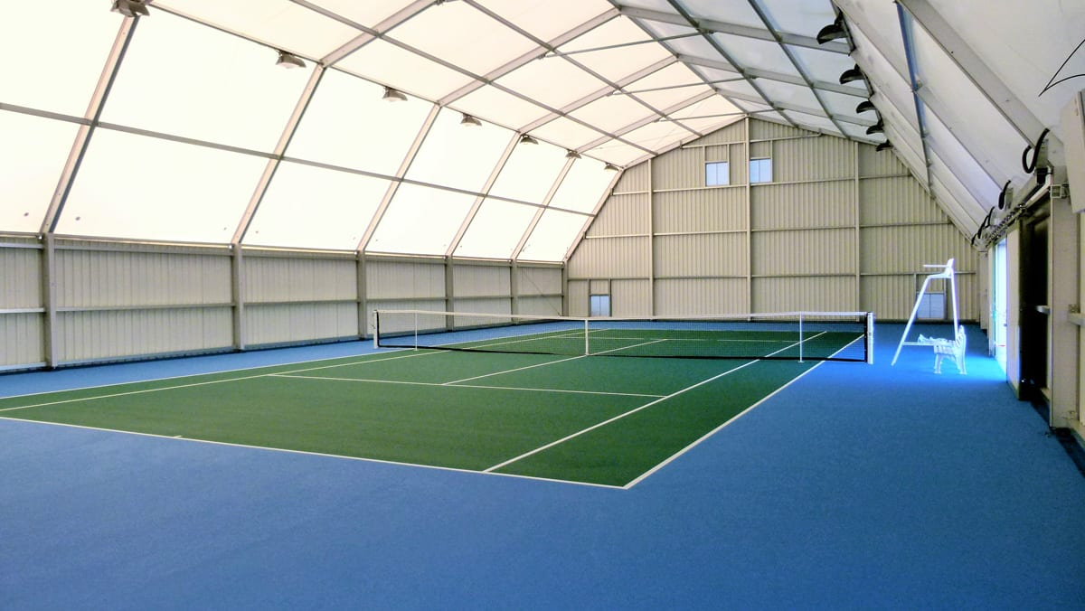 A Large canopy with corrugated steel sheet walls for an indoor tennis court
